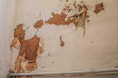 Sich von der Wand lösende Tapete und Blasen im Anstrich
