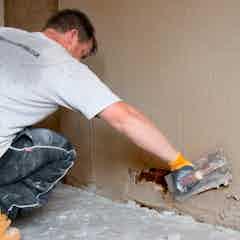 Eine zweite Schicht Putz auf die Wand auftragen